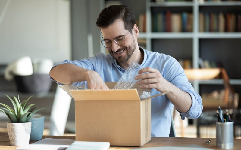 Man packing parcel with bubble wrap